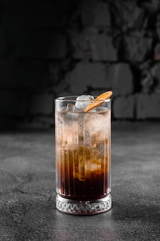 Cocktail in glass with cola, alcohol, ice, decorated dried orange on gray surface.