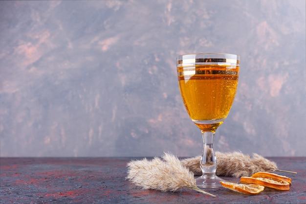 Bicchiere da cocktail con succo di frutta fresco e fette di limone essiccate su fondo di marmo.