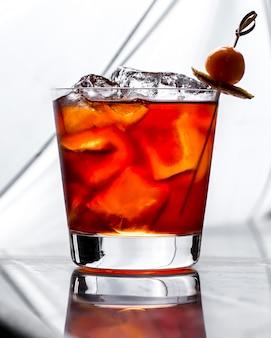 Un bicchiere da cocktail con cubetti di ghiaccio guarnito con limone secco e frutta in bianco