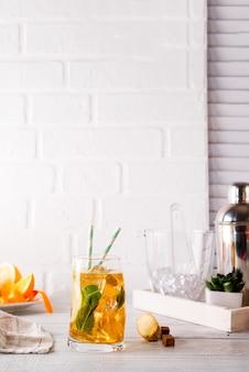 白い木製のバックグラウンドに氷、ミント、ジンジャーを持つカクテルグラス
