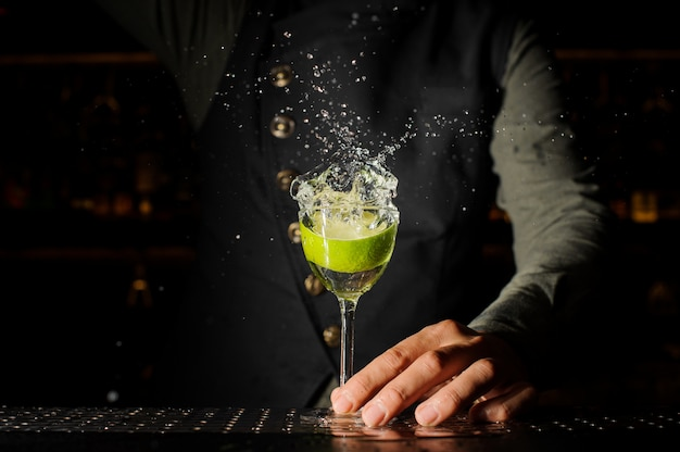 Cocktail glass with splashing alcoholic drink and lime in it