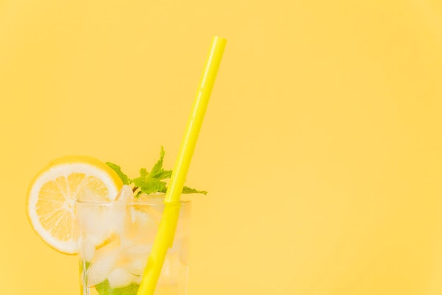 Cocktail glass with straw and lemon on yellow background