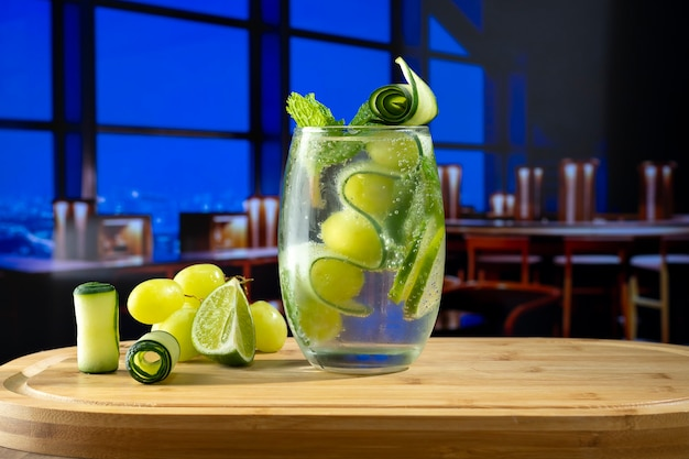A cocktail glass on a wooden board decorated with cucumber grapes mint and a picture of a bar in