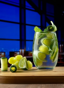 A cocktail glass on a wooden board decorated with cucumber grapes mint and a picture of a bar