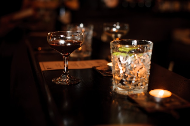 Cocktail glasses filled with alcoholic drinks on the bar counter