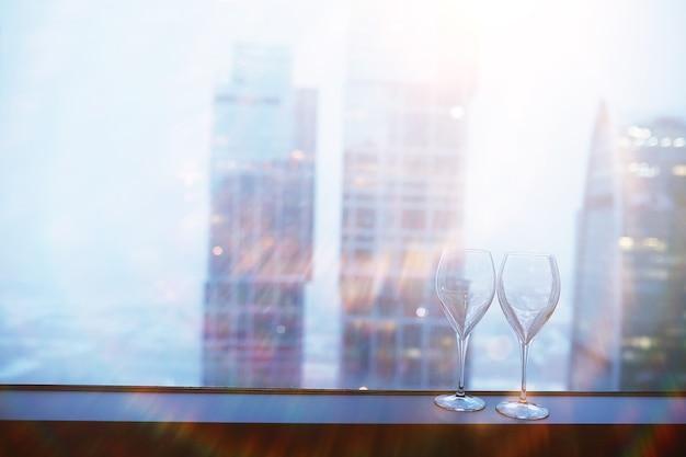 高層ビルのガラスのそばの窓辺のカクテルグラス