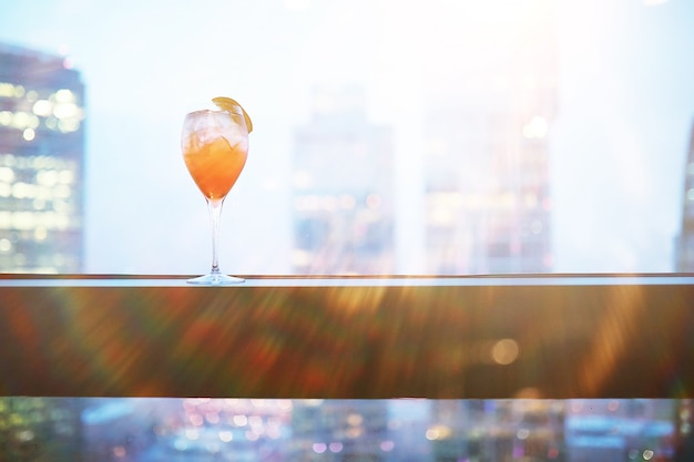 Cocktail glasses on the windowsill by the glass of a tall building
