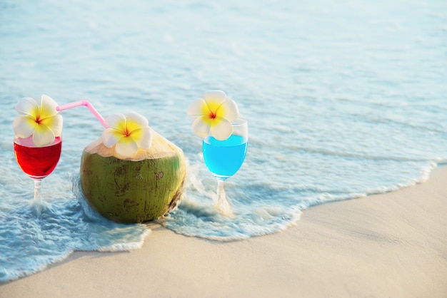 Cocktail glasses with coconut and pineapple on clean sand beach - fruit and drink on sea beach