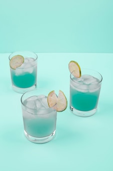Cocktail glasses with ice cubes and lemon slice on mint background