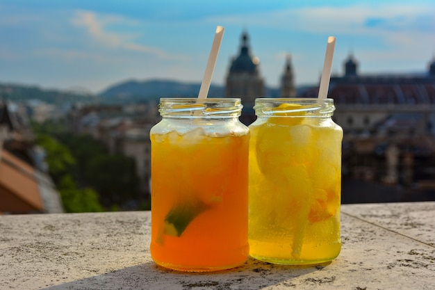 Cocktail glasses with refreshing lemonade on table in rooftop bar against city view