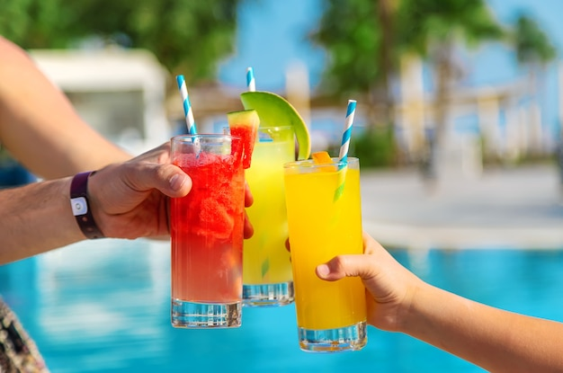 Cocktail in the hands of the family near the pool