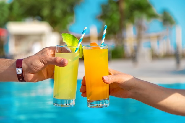 Cocktail in the hands of the people near the pool