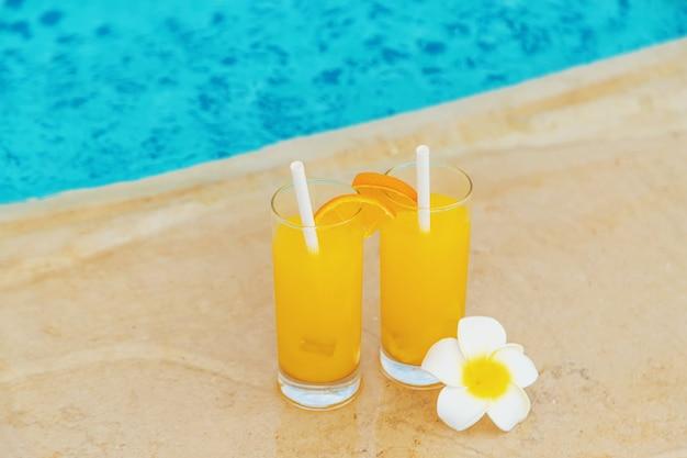 プールサイドのグラスとフルーツのカクテル