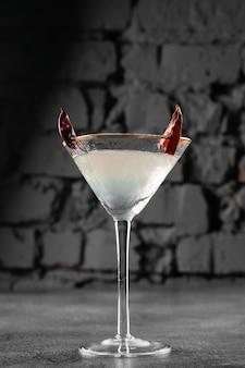 Коктейль в стакане с чили на серой поверхности. дьявольский алкогольный напиток.