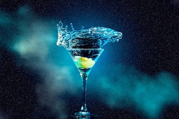 Коктейль в бокале с вкраплениями и лимоном на темном дымном фоне вечеринка клуб развлечения