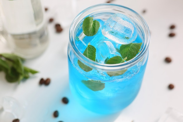 The cocktail is blue in a jar with mint and ice. image with depth of field.