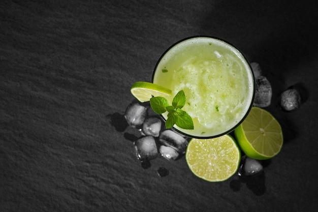 ライム、ミント、氷のカクテルジュース。黒のテーブルの背景にバードリンクアクセサリー。