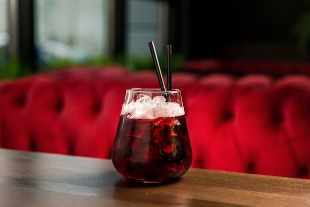 A cocktail in a lowball, old fashioned, rocks glass, with ice, rum coca-cola