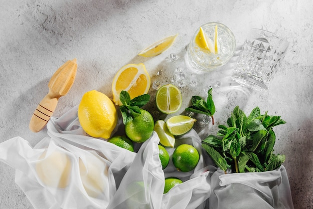 Приготовление коктейлей. мята, лайм, лимонные ингредиенты для льда и барная посуда. плоская планировка, вид сверху.