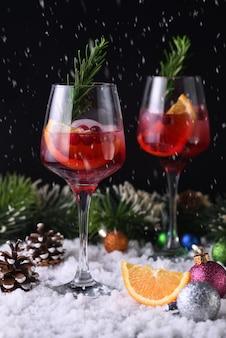 Коктейль маргарита с клюквой, апельсином и розмарином. идеальный коктейль для рождественской вечеринки Premium Фотографии