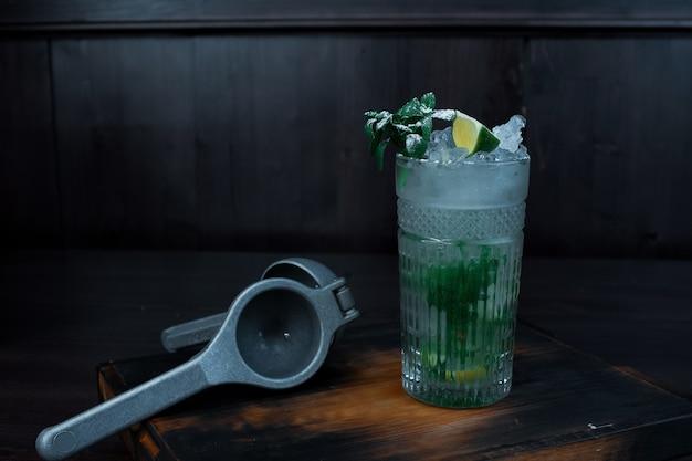 カクテル「モヒート」は、レモンジュースを手に入れるための楽器の隣にあるバーのヴィンテージテーブルの上に立っています。おいしいお酒。