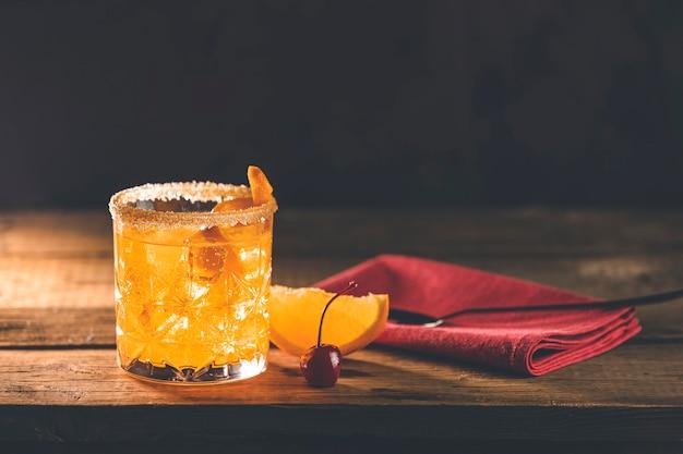 古い木の板にカクテルネグローニ。ジン、カンパリマティーニロッソ、オレンジと一緒に飲む、イタリアカクテル、食前酒、1919年にイタリアのフィレンツェで最初に混合されたアルコールビターカクテル