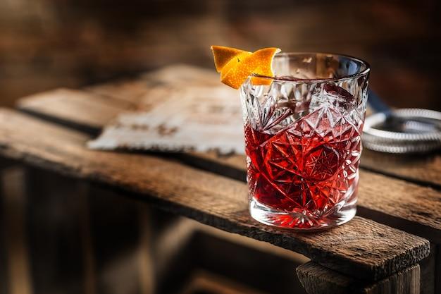 Коктейль негрони на старой деревянной доске. напиток с джином, кампари мартини россо и апельсином.
