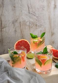 Коктейль из выжатого сока красного грейпфрута и нежного лимона, базилика, лайма и охлажденных кубиков льда