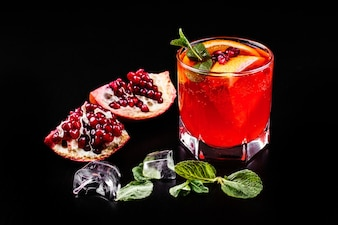 Cocktail of vodka, grenadine, pomegranate, ice and mint stands on a black table