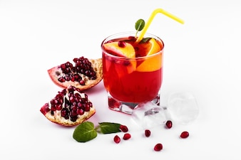 Cocktail of vodka, grenadine, pomegranate, ice and mint stands on a white table
