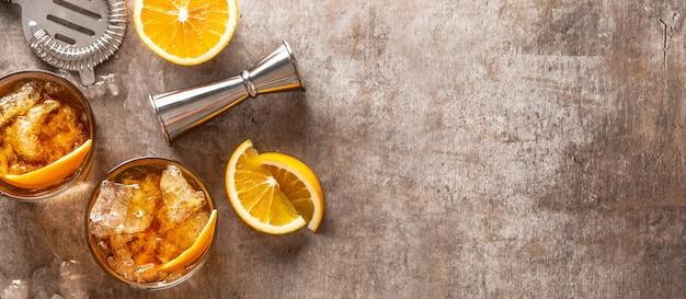 カクテルバーカウンターにオレンジ色の昔ながらのネグローニ-ビューの上部。