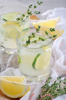 진 레몬 주스 또는 라임 주스와 타임 노트를 기반으로 한 칵테일 여름날 상쾌한 칵테일을 즐기세요