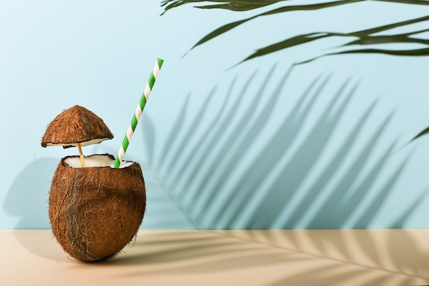 Cocktail in an open coconut and the shadow of palm leaves on colored. summer mood, harvesting.