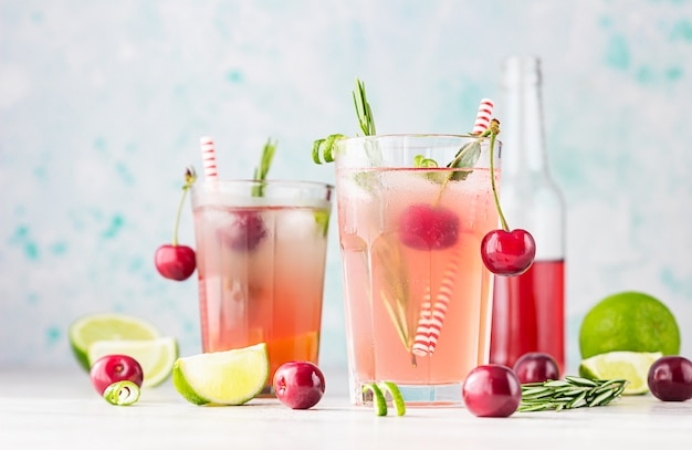 カクテルやチェリー、ライム、灰色のテーブルにローズマリーとレモネード。夏の飲み物。