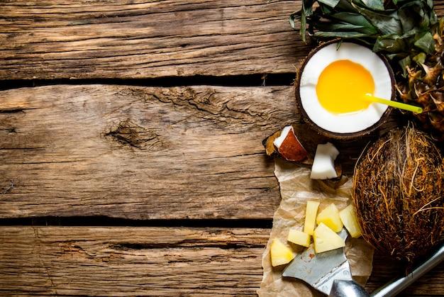 カクテルピニャコラーダ。木製のテーブルの上にココナッツラム酒とパイナップルのカップで新鮮なカクテル。テキスト用の空き容量。上面図