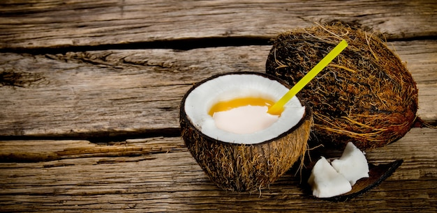 Cocktail pina colada. a fresh cocktail in coconut cup on wooden table. free space for text.