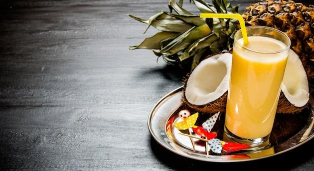 カクテルピニャコラーダ。黒板にパイナップル、ココナッツ、ラム酒を使ったカクテルを作ります。テキスト用の空き容量。