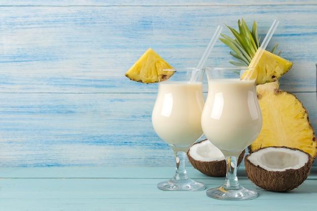 칵테일 피나 콜라다. 피나 콜라다 근처에서 코코넛 밀크와 파인애플 주스를 곁들인 상쾌한 여름 알코올 칵테일. 여름 음료. 칵테일 준비. 푸른 나무 테이블에.