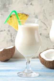 Коктейль пина колада. рядом - освежающий летний алкогольный коктейль пина колада с кокосовым молоком и ананасовым соком. летний напиток. приготовление коктейлей.