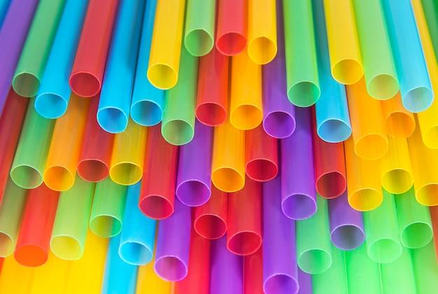 さまざまな色のカクテルプラスチックチューブが抽象的な背景とテクスチャをクローズアップ