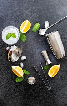 Cocktail shaker and bar tools. ingredients for a cold alcoholic cocktail. mojito cocktail. lemon, mint, ice, rum. top view, vertical, black background, copy space