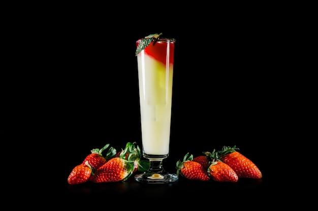 Cocktail e fragole su sfondo nero