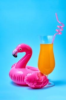 Коктейль текила санрайз с надувной игрушкой для бассейна с розовым фламинго на синем фоне летней концепции