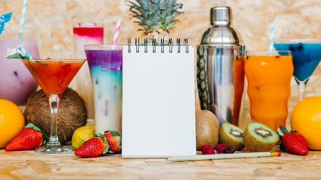 Cocktail and tropical fruits with blank notepad