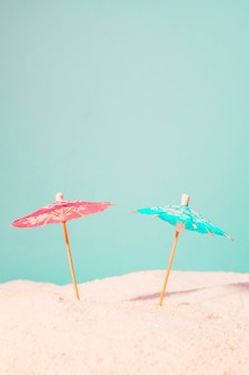 Cocktail umbrellas in sand