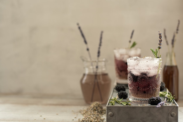 Cocktail with berries and lavender syrup on a light background
