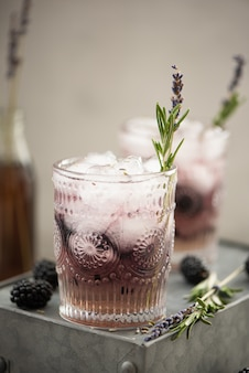 Cocktail with berries and lavender syrup on a light wall
