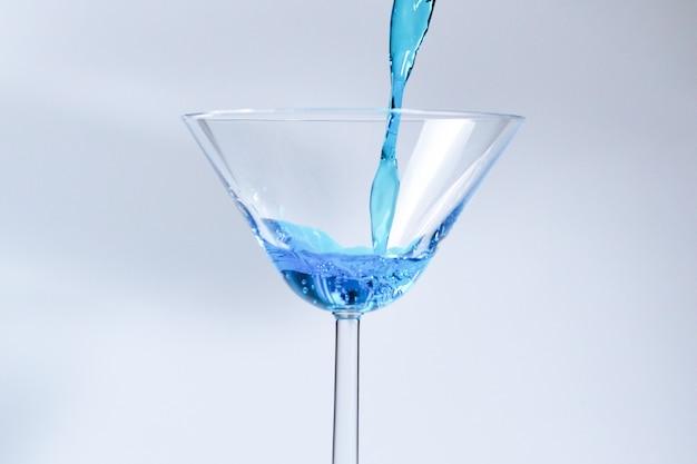 ガラスの青い液体とカクテル。水しぶきと滴の液体を注ぐ青い水とガラス。白い背景の上の水しぶきとアルコールで満たされたマティーニグラス。さわやかな飲み物のコンセプト。