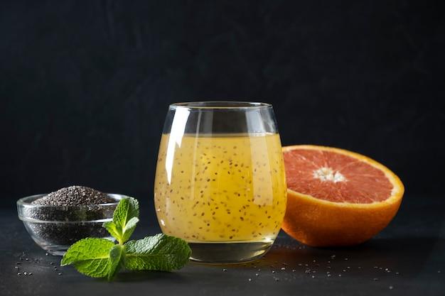 チア種子と黒のガラスのオレンジジュースのカクテル。閉じる。