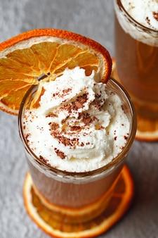 クリームとオレンジのカクテル。オレンジジュースとドライオレンジ